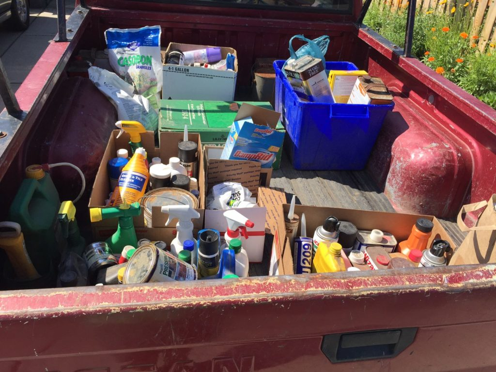 Hazardous waste containers in varying sizes, piled into back of pickup truck