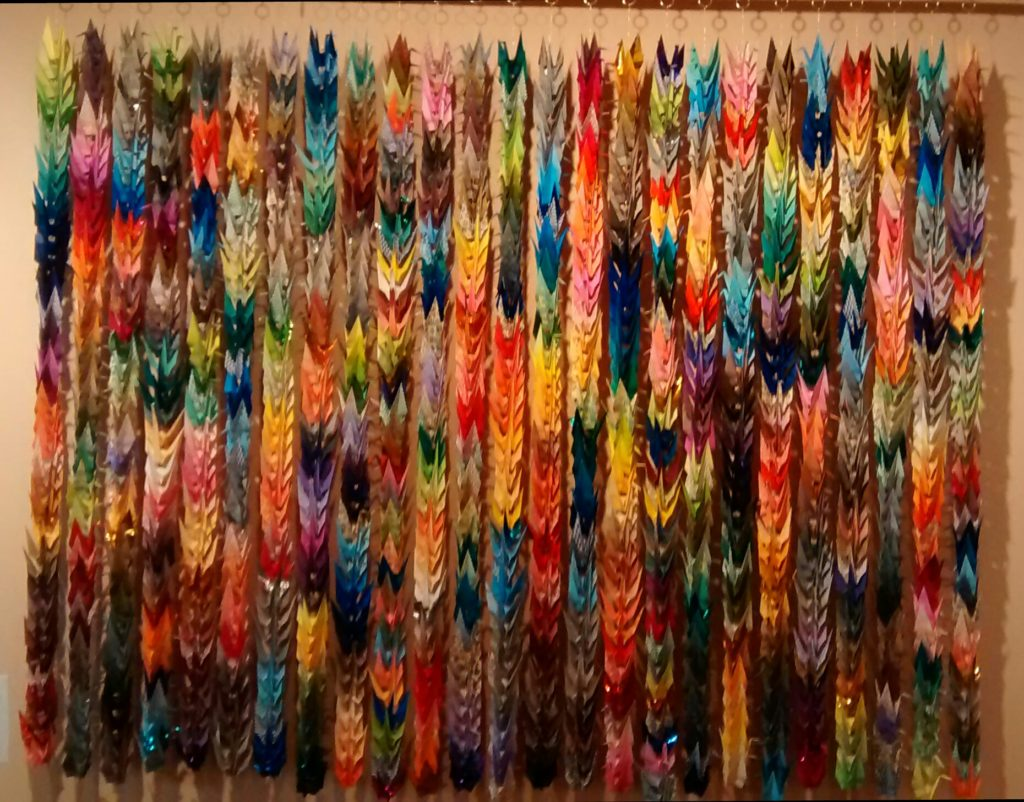 Folded paper cranes, affixed to wall in hanging rows from hooks