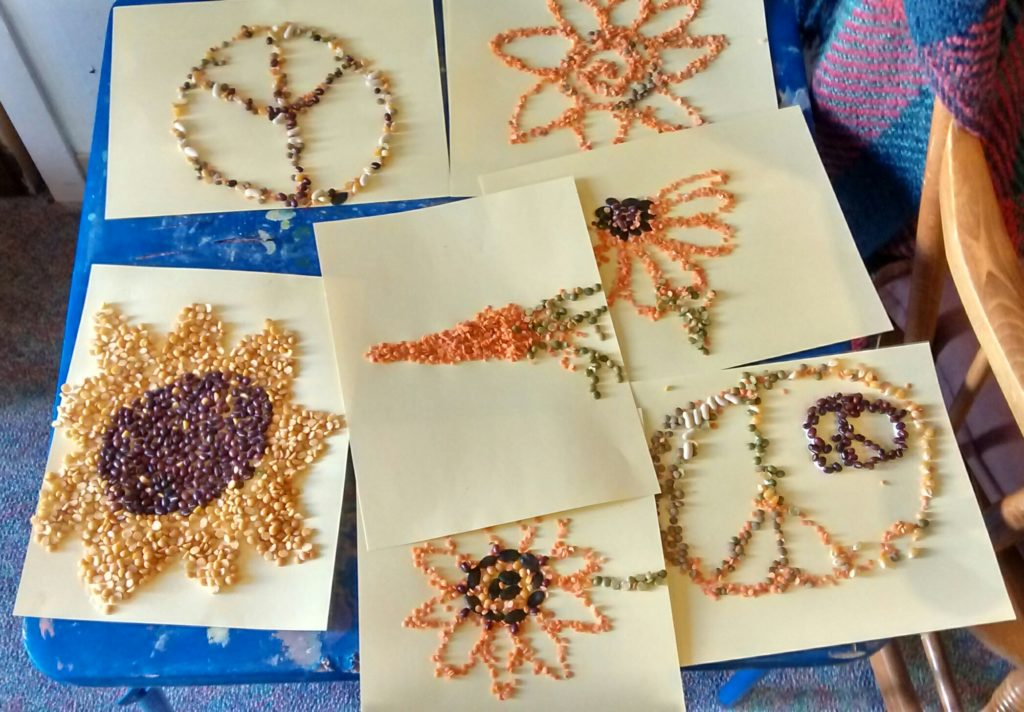 Sheets of paper, with seeds attached to them in pictorial representations of flowers and peace symbols