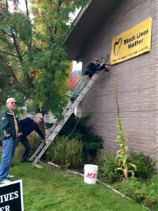 Three men from L to R: one looking toward camera, one standing at base and stabilizing a ladder that is propped against an exterior building wall, and one man perched on top of ladder attaching black-on-yellow 'Black Lives Matter' banner to the wall