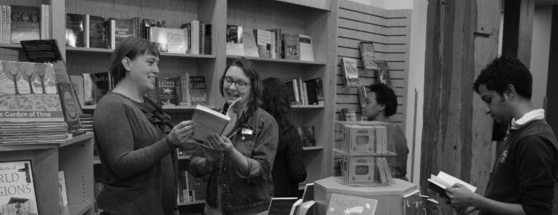 Black-and-white image of people reading in bookstore